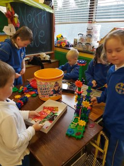Kids making toy machines with magnets and gears
